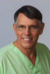 Smiling Dr. W. Keith deJong in green scrubs
