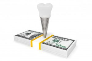 dental implant on top of stack of cash